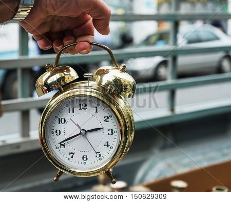 vintage clock alarm clock golden hand holding on the city background