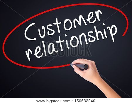 Woman Hand Writing Customer Relationship With A Marker Over Transparent Board