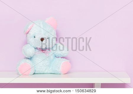 Blue teddy bear on shelf. White doll bear on the pink background.