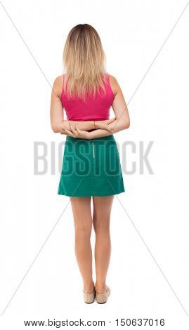 back view of standing young beautiful  woman.  girl  watching. Rear view people collection.  backside view of person.  Girl in green skirt standing with her hands folded on her back