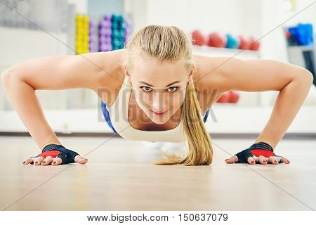 Active athletic young woman doing push-ups. Healthy lifestyle. Fitness, aerobics, bodybuilding.