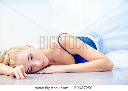 Portrait of a professional ballet dancer lying on a floor. Female ballerina having a rest after performance or rehearsal. Ballet concept.