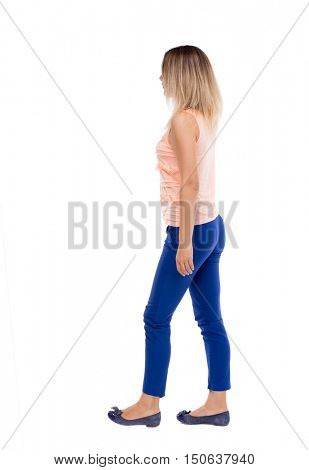 back view of walking  woman. beautiful girl in motion.  backside view of person.  Rear view people collection. Isolated over white background. The blonde in a pink t-shirt goes sideways.