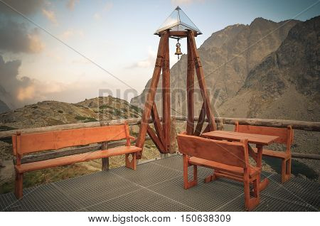 Wooden bell and benches with mountains in the background. Resting place in front of the hut in the High Tatra Slovakia.