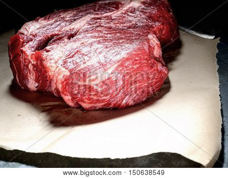 marble raw beef on a paper, on a gray background