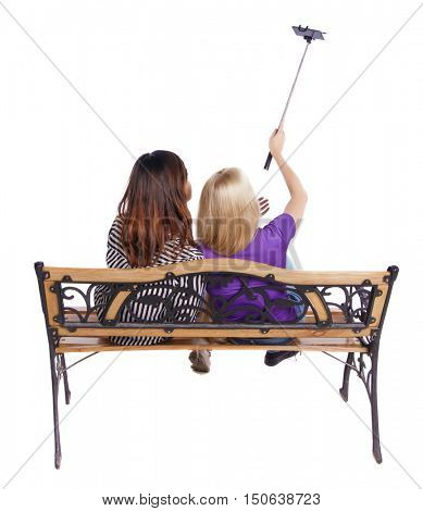 Back view of two women to make a selfie stick portrait sitting on the bench. Rear view people collection. backside view of person. Isolated over white background. A couple of girls photographed using