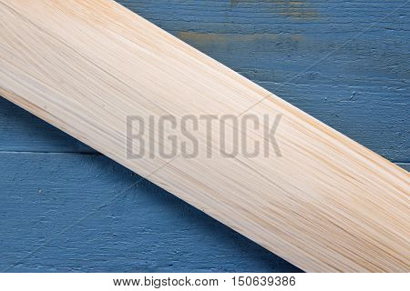 Pine board on a blue wooden background. Copy space for text.