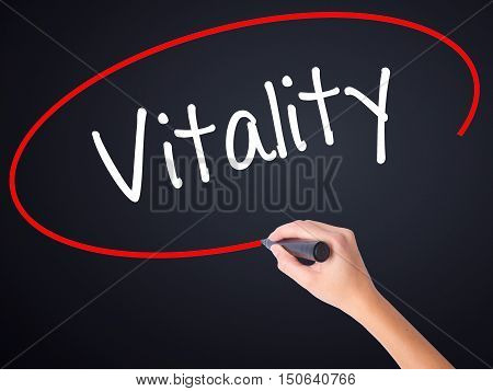 Woman Hand Writing Vitality  With A Marker Over Transparent Board .