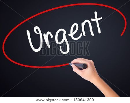 Woman Hand Writing Urgent With A Marker Over Transparent Board .