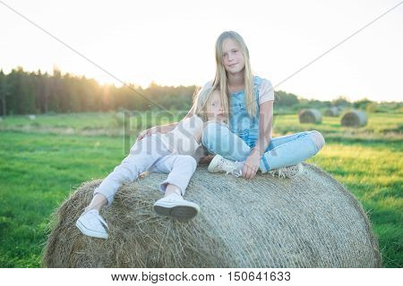 Beautiful Young Girls Sitting On The Haystack