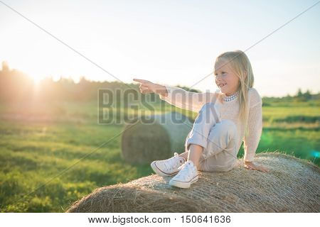 Beautiful young girl sitting on the haystack in the field