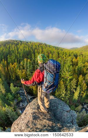 Man With Backpack And Trekking Pole In Bandana Standing On A Rock At Dawn On A Background Autumn For