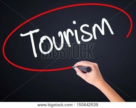 Woman Hand Writing Tourism With A Marker Over Transparent Board .