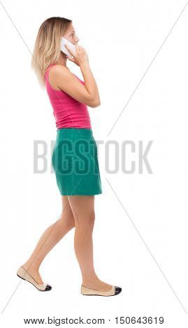 side view of a woman walking with a mobile phone. back view ofgirl in motion.  backside view of person.  Rear view people collection. Isolated over white background. Girl in a green skirt misses