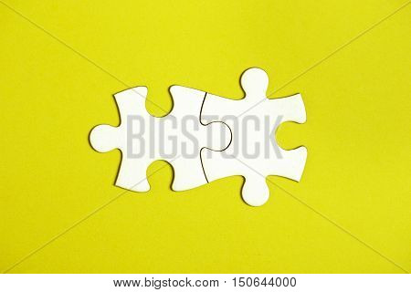 Two connected jigsaw puzzle pieces on yellow background. The concept of finding the right solutions in teamwork.