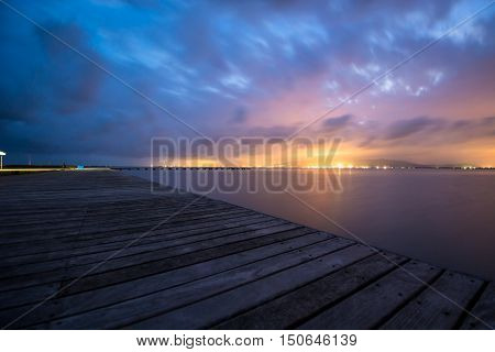 Distant city lights watched from a wooden pier.