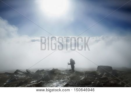 Mountaineer reaches the top of mountain in fog and autumn morning sun. Carpathian Mountains.Ukraine.
