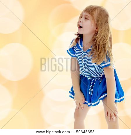 On a brown background with white blurred circles. Cute little unkempt girl in a short blue dress. Girl looking to the side with his hands on his knees.