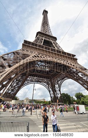PARIS FRANCE - JULY 25 2011: People walk in front of Eiffel Tower in Paris France. Eiffel Tower was the tallest building in the world from 1889 to 1930. It is a major landmark in Paris.