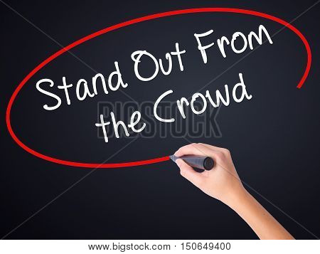 Woman Hand Writing Stand Out From The Crowd With A Marker Over Transparent Board