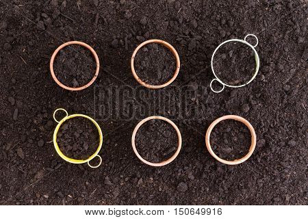 Six Neatly Arranged Planters Filled With Soil