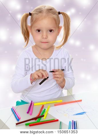 Pretty little blonde girl drawing with markers at the table.Girl holding in hands blue marker.The concept of celebrating the New year, Holy Christmas, or child's birthday on a purple background