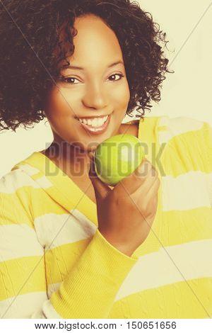 Beautiful smiling black woman eating apple