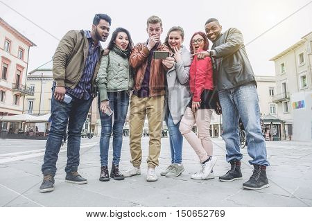 Multiracial group of people looking surprised smart phone - Young mixed race friends having fun in city center - New technology trends addiction concept - Warm raw filter