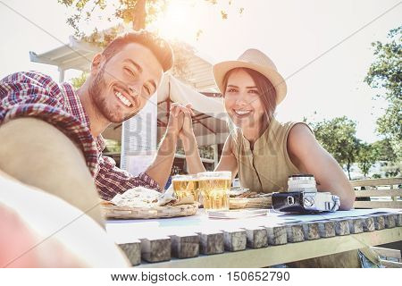 Handsome couple taking selfie with mobile smart phone camera - Young fashion tourist making photo souvenir while eating meal at bar street food restaurant - Vacation and love concept - Warm filter