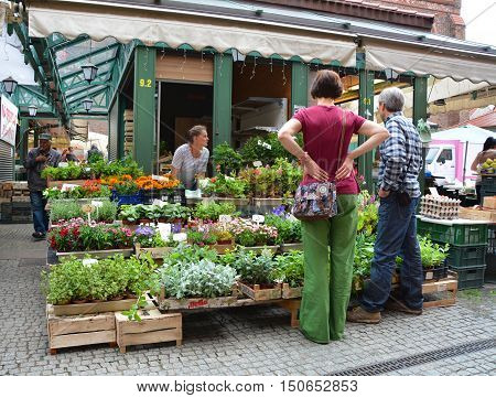 GDANSK POLAND - JUNE 27 2015: People shop at the herbs and flowers stall market in old town. Gdansk has one of the largest seaports on the Baltic Sea