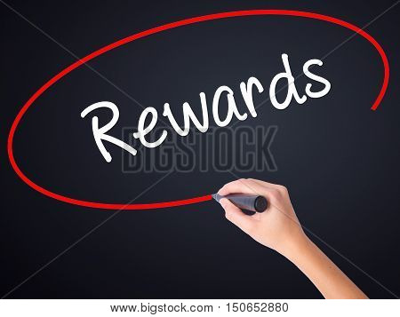 Woman Hand Writing Rewards With A Marker Over Transparent Board