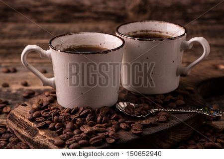 Cup of cofee with coffee beans on a wood table close up photo