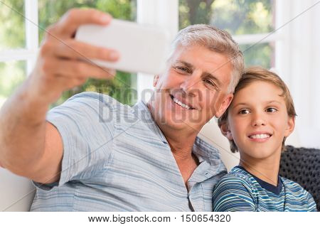 Smiling grandfather with grandson taking selfie with mobile phone. Grandchild taking selfie with smiling grandpa. Portrait of grandfather with grandson sitting on sofa at home.
