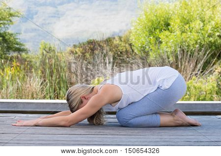Woman in sports clothes performing yoga in child pose. Relaxed senior woman exercising yoga asana. Mature woman stretching while practicing yoga outdoor.