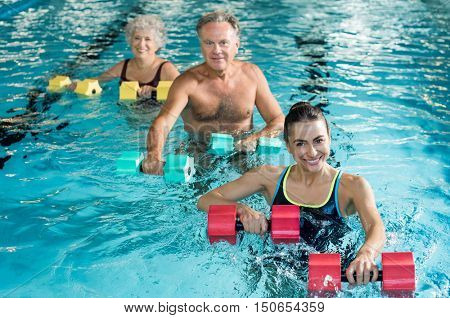 Happy active fitness mature man and senior woman doing exercise with aqua dumbbell in a swimming pool with instructor. Retired people doing aqua gym exercise with water dumbbell and looking at camera.