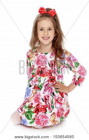 Gentle little girl with a long ponytail down to his shoulders, and a red bow on her head, in a beautiful summer dress. The girl kneeling on the floor.  - Isolated on white background