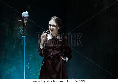 Portrait of a young girl with drop counter as a vampire woman against school board . The image in the style of Halloween