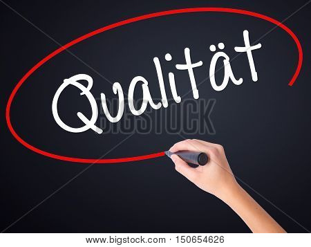 Woman Hand Writing Quality (qualitat In German) With A Marker Over Transparent Board