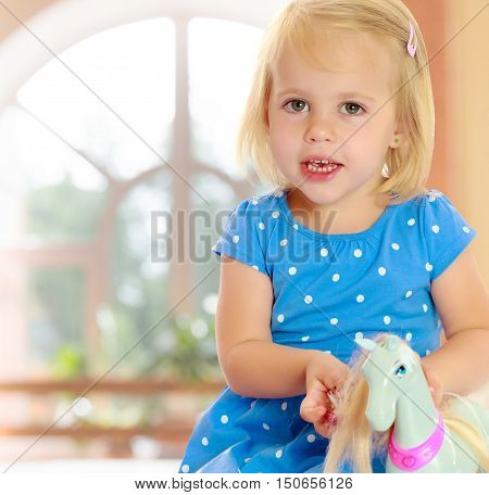 On the background of the hall with large semi-circular window.Cute little blonde girl playing with a toy horse. Girl wearing a blue dress with polka dots.