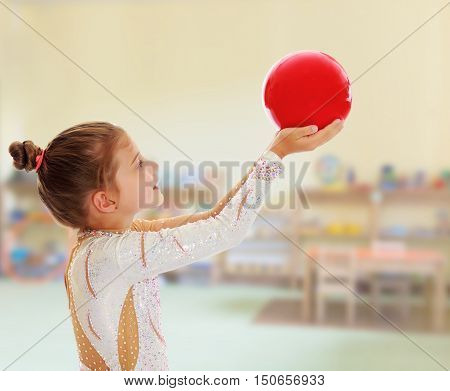 Cute little girl gymnast turned sideways to the camera , holding in his outstretched hands a red ball.On the background of the room where children live, and are on the shelves of toys.11