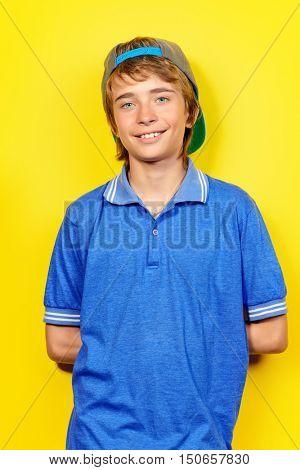 Portrait of a smiling teenage boy over yellow background. Studio shot. Teen fashion.