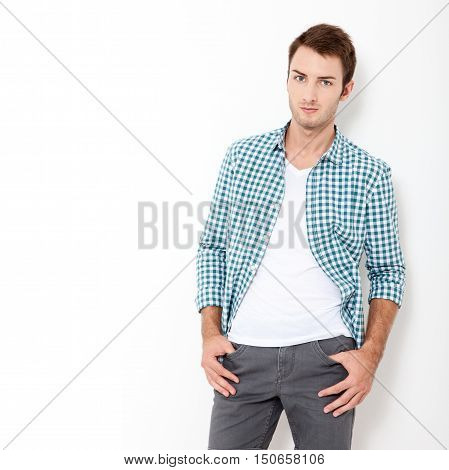 Happy young man. Portrait of handsome young man in casual shirt keeping arms crossed and smiling while standing against white background