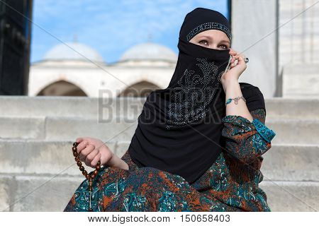 Outdoor Portrait of Lady talking on Telephone and holding Rosary in Traditional Islamic Clothing sitting at Marble Stairs of Mosque with Domes and Minarets Background