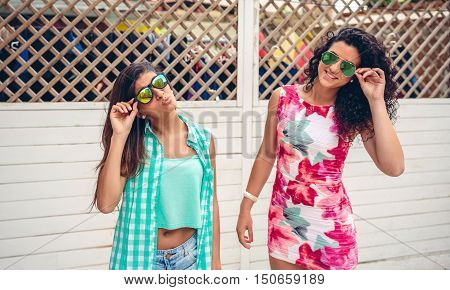 Portrait of two happy young women with sunglasses looking at camera over white garden fence background