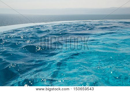 Photo of the Water texture in infinity swimming pool. Paradise resort concept. Seaview.