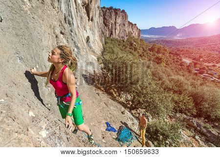 Young talented Female Rock Climber ascending rocky Wall Male Team Partner belaying her with blue Rope below unusual Nature Landscape Mountains and Forest on Background