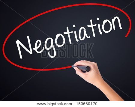Woman Hand Writing Negotiation  With A Marker Over Transparent Board .