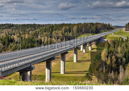 Highway bridge over russian forest in landscape sunny summer day.