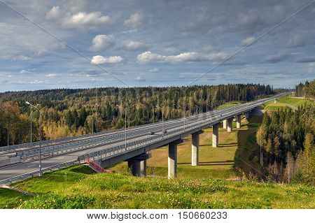 Steel bridge overpass on concrete supports highway crosses Russian forest sunny summer day.