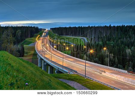 Overpass and light trails at night on the illuminated highway in forest.